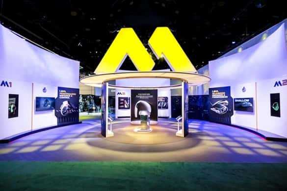 A tradeshow booth with a large yellow neon letter M above it