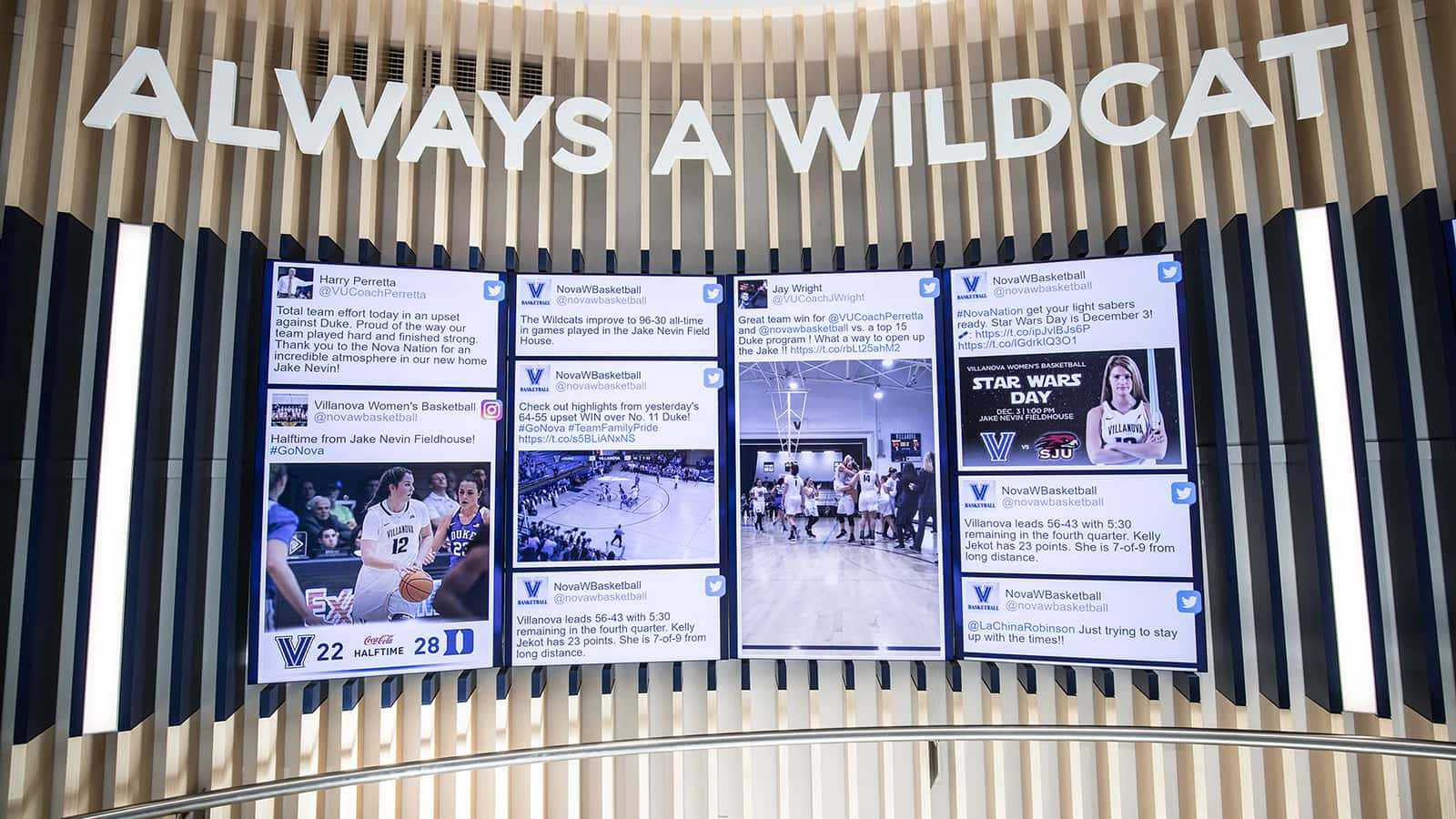 Men's and women's head basketball coaches twitter feeds in the center of the media wall in the atrium of the Villanova Davis Center.