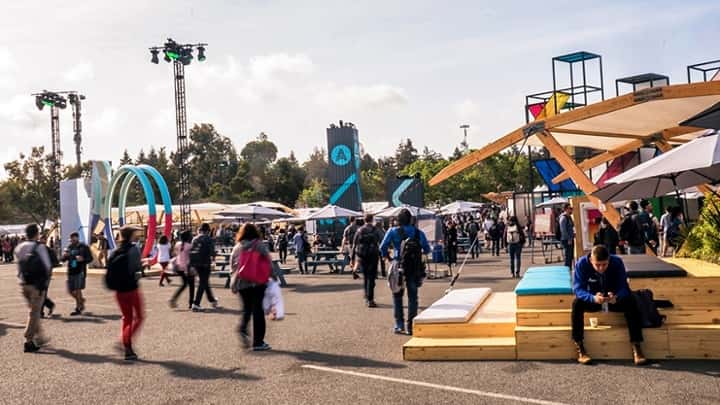 Crowd of People walking through multiple white tents with a blue and gray tower in background